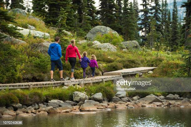 family enjoying a hike in the mountains - thoroughfare stock photos and pictures