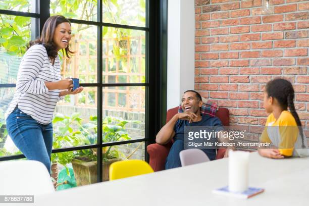 Family enjoying against window at home