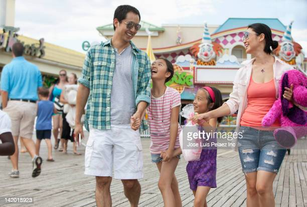 family enjoying amusement park - boardwalk stock pictures, royalty-free photos & images