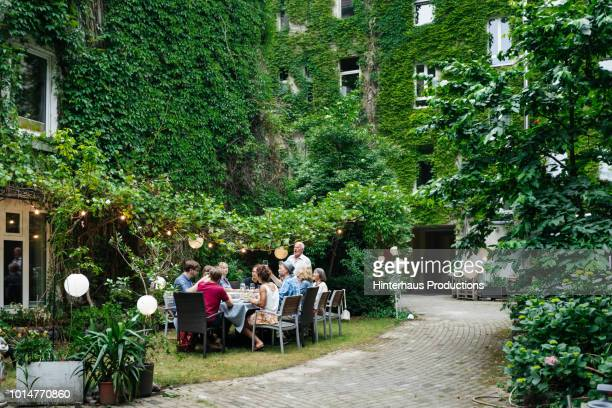 family enjoying an outdoor meal together - outdoor party stock pictures, royalty-free photos & images