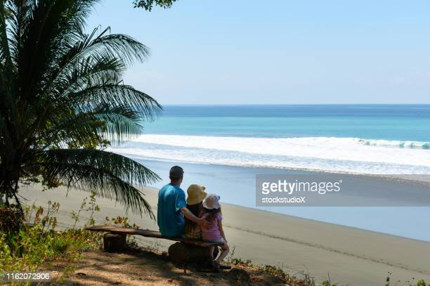 Family enjoying at beach while sitting on bench