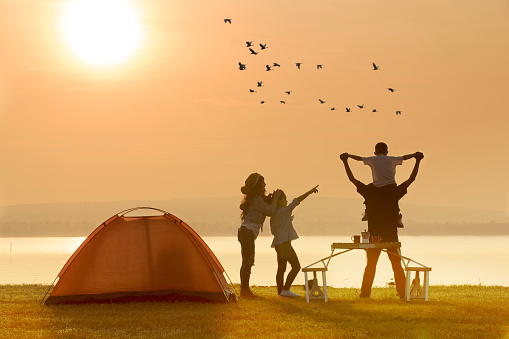 Family Enjoying At Campsite By Lake During Sunset - gettyimageskorea