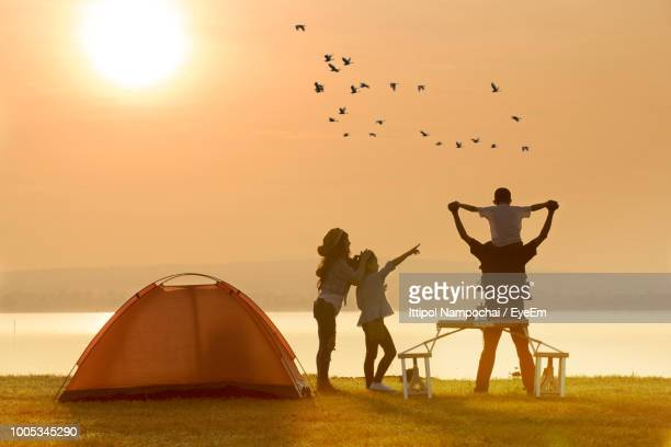 family enjoying at campsite by lake during sunset - camping stock photos and pictures