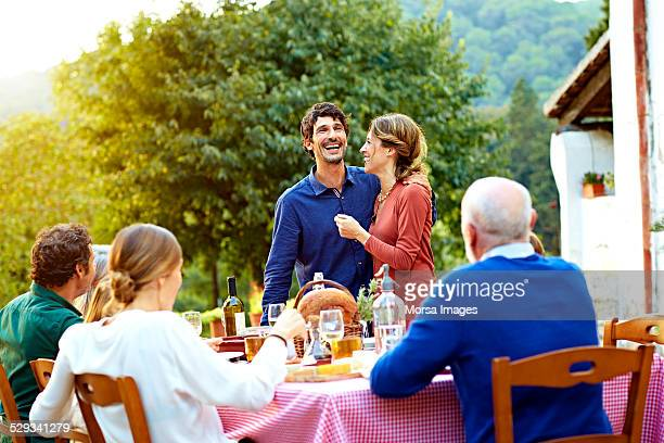 family enjoying at outdoor meal table in yard - sólo con adultos fotografías e imágenes de stock