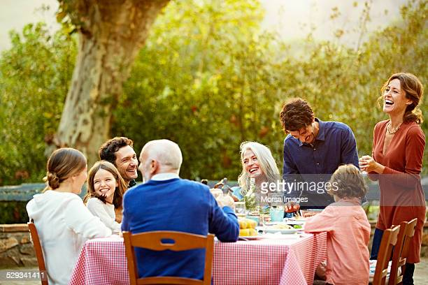 Family enjoying at outdoor meal table in yard
