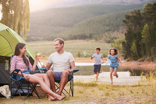 Family Enjoying Camping Vacation By Lake Together 969586708
