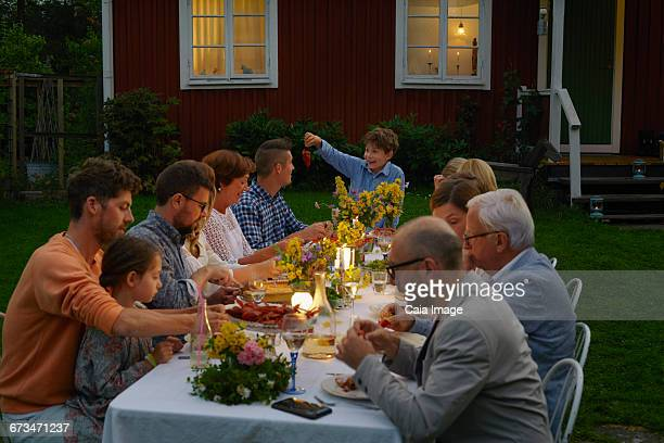 Family enjoying candlelight garden dinner party