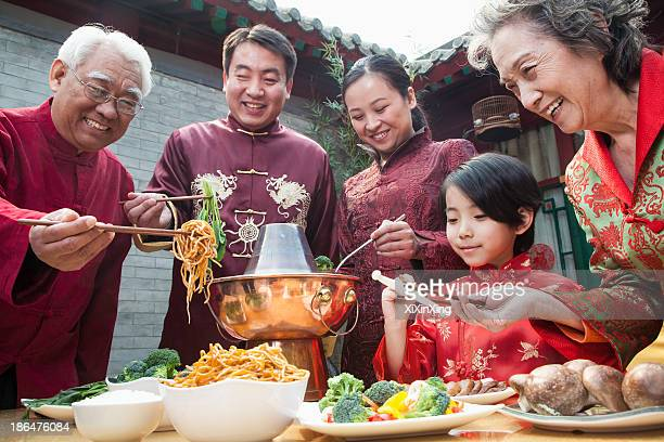 family enjoying chinese meal in traditional chinese clothing - traditionele kledij stockfoto's en -beelden