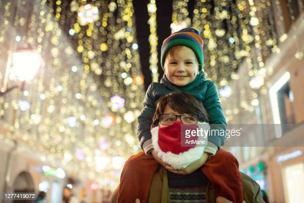 family enjoying christmas lights at a city street during covid-19 pandemic - coronavirus winter stock pictures, royalty-free photos & images