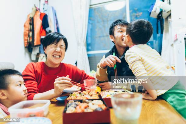family enjoying eating together - japanese culture stock pictures, royalty-free photos & images