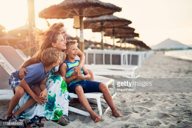 family enjoying evening on beach - férias imagens e fotografias de stock