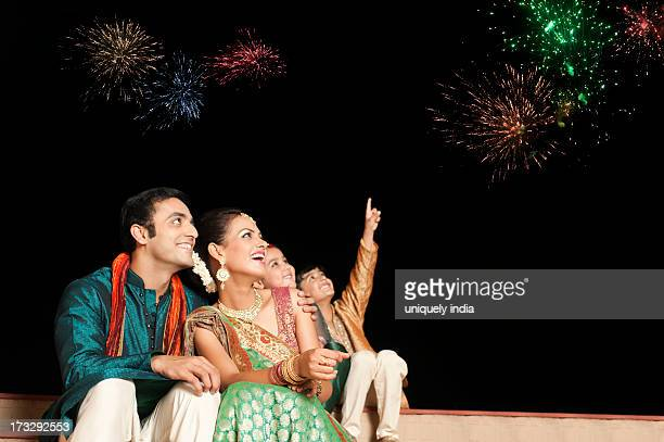 family enjoying firework display on diwali - diwali celebration stock photos and pictures