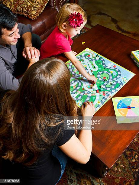 family enjoying game night together - game board stock photos and pictures