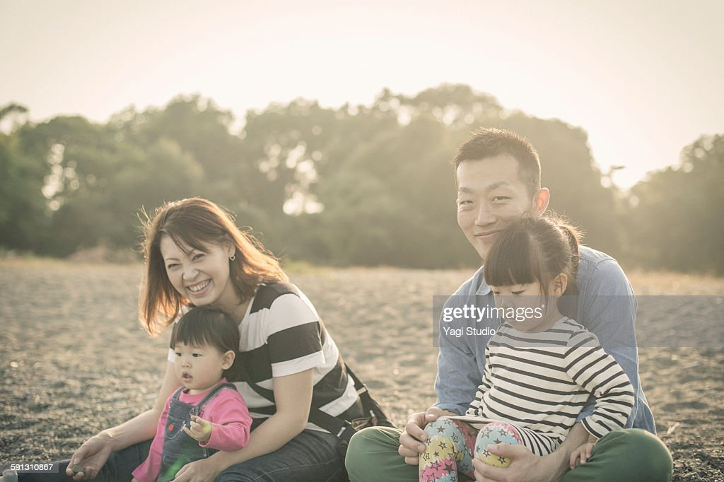 Family enjoying in front of the lake shore : Stock Photo