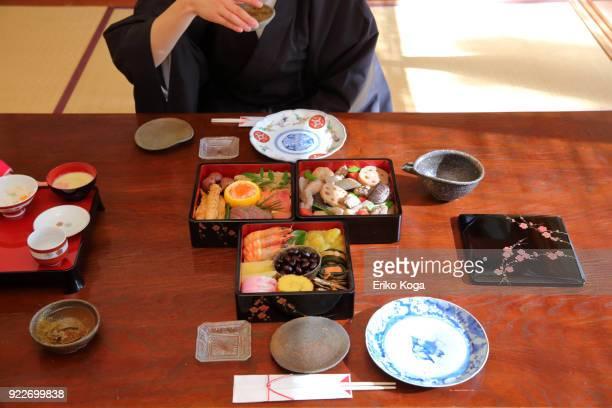 family enjoying japanese new year's dish called osechi and sake - おせち料理 ストックフォトと画像