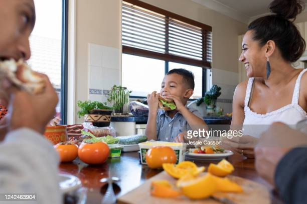 family enjoying lunch around the dining table - new zealand stock pictures, royalty-free photos & images