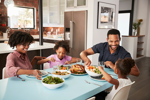 Family Enjoying Meal Around Table At Home Together 992108418
