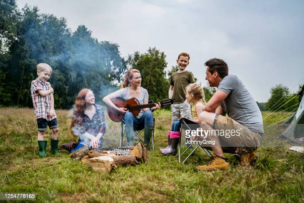 family enjoying mother playing guitar during camping trip - guitarist stock pictures, royalty-free photos & images