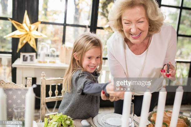 family enjoying preparing christmas - christmas decore candle stock pictures, royalty-free photos & images