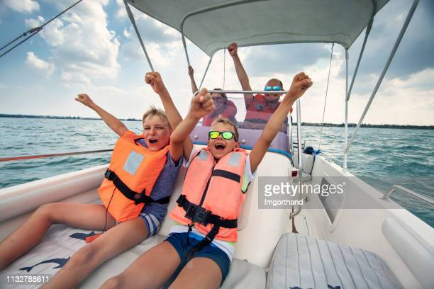 family enjoying riding a boat on lake garda - sailor stock pictures, royalty-free photos & images