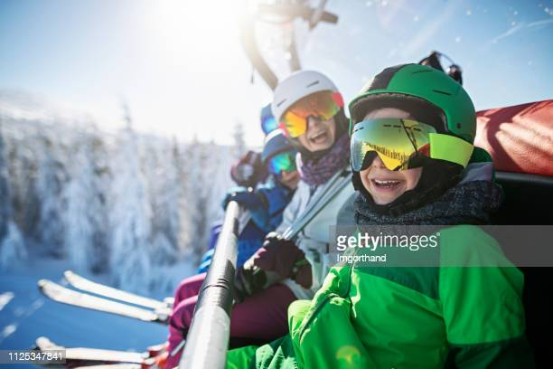 family enjoying skiing on sunny winter day - ski lift stock pictures, royalty-free photos & images