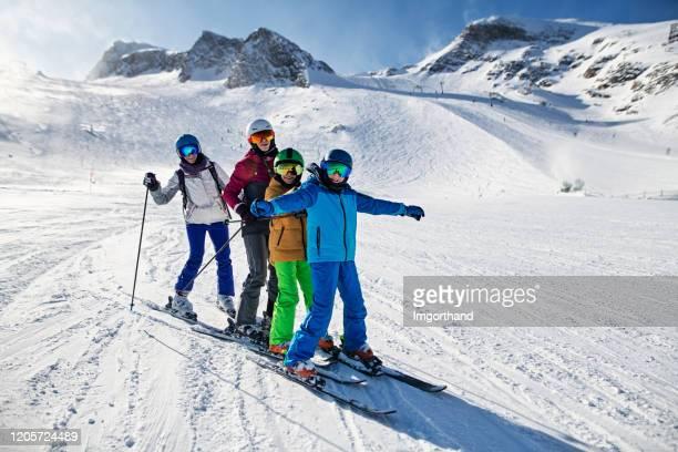 familie beim gemeinsamen skifahren am gletscher in den alpen - skifahren stock-fotos und bilder