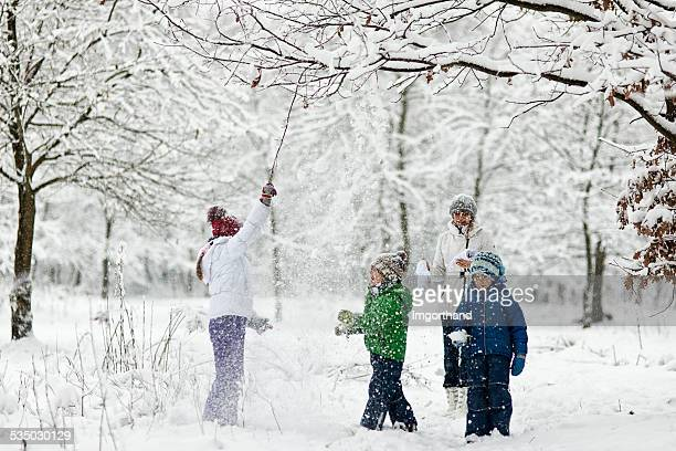 Family enjoying snow in forest.