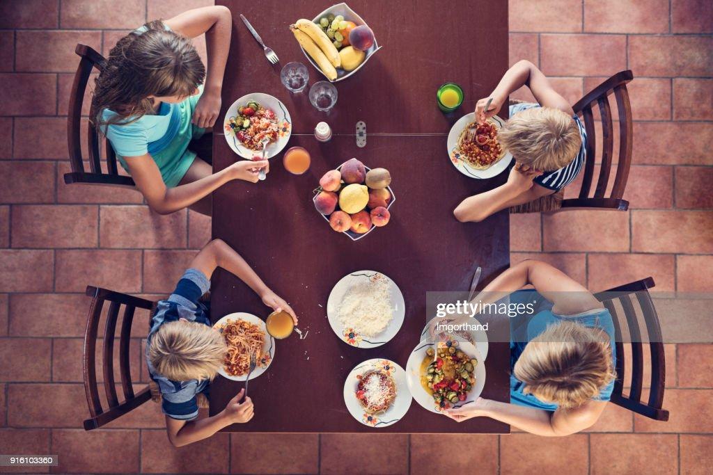 Family enjoying spaghetti lunch : Stock Photo