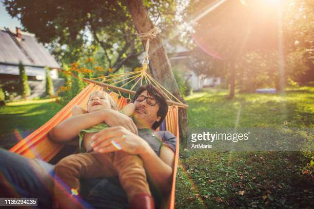 family enjoying spring/summer day in hammock - hammock stock pictures, royalty-free photos & images