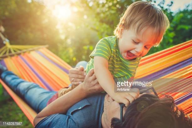 famille appréciant le jour de printemps/d'été dans le hamac - printemps humour photos et images de collection