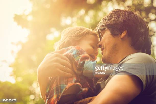 family enjoying summer in park - modern manhood stock pictures, royalty-free photos & images