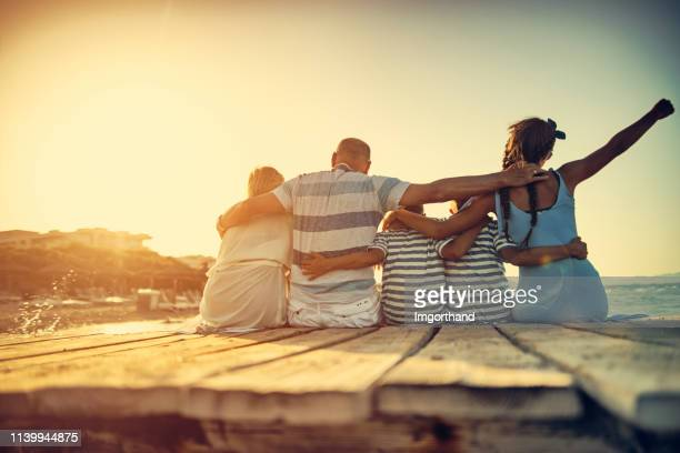 family enjoying sunset on beach vacations - jetty stock pictures, royalty-free photos & images