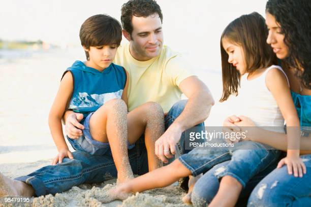 family enjoying the beach - mom sits on sons lap stock pictures, royalty-free photos & images