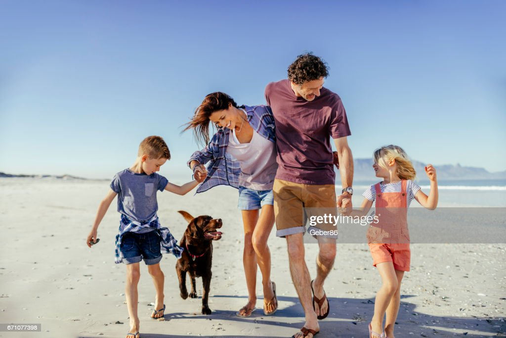 Family enjoying time on the beach : Stock Photo