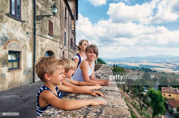 family enjoying tuscany view from volterra terrace - volterra stock photos and pictures