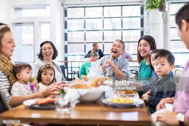 Family enjoying while having lunch at restaurant