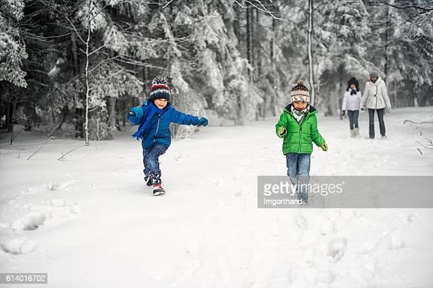 Family enjoying winter walk in forest.