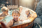 Family enjoying wood fired barrel hot tub in the back yard
