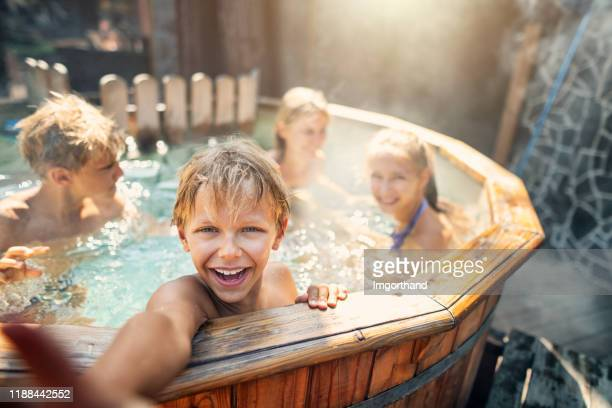 family enjoying wood fired barrel hot tub in the back yard - hot tub stock pictures, royalty-free photos & images