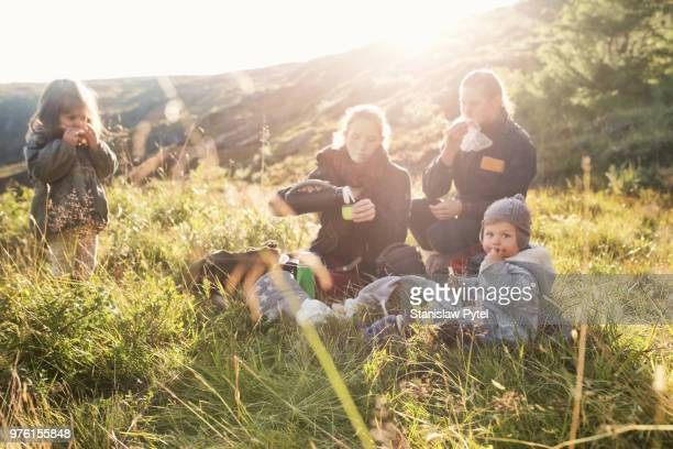 Family enjoyng meal when trekking in mountains at sunset