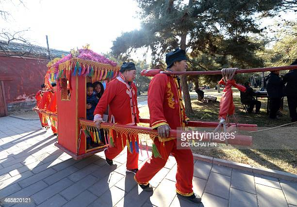 A family enjoys a sedan chair ride at the Ditan park temple fair in Beijing on January 30 on the eve of the Lunar New Year Over a billion Chinese in...