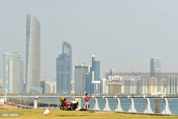 A family enjoys an afternoon view from Abu Dhabi Marina on Abu Dhabi beach and Al Hosn and Al Danah skyscrapers in the backgroun On Friday February...