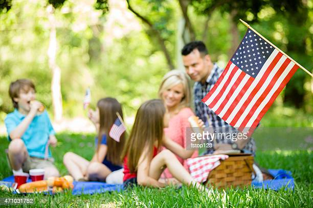 Family enjoys July 4th picnic in summer season. American flag.