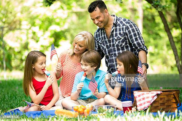 family enjoys july 4th picnic in summer season. american flags. - labour day stock photos and pictures