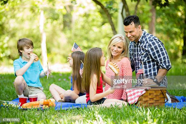 Family enjoys July 4th picnic in summer season. American flags.