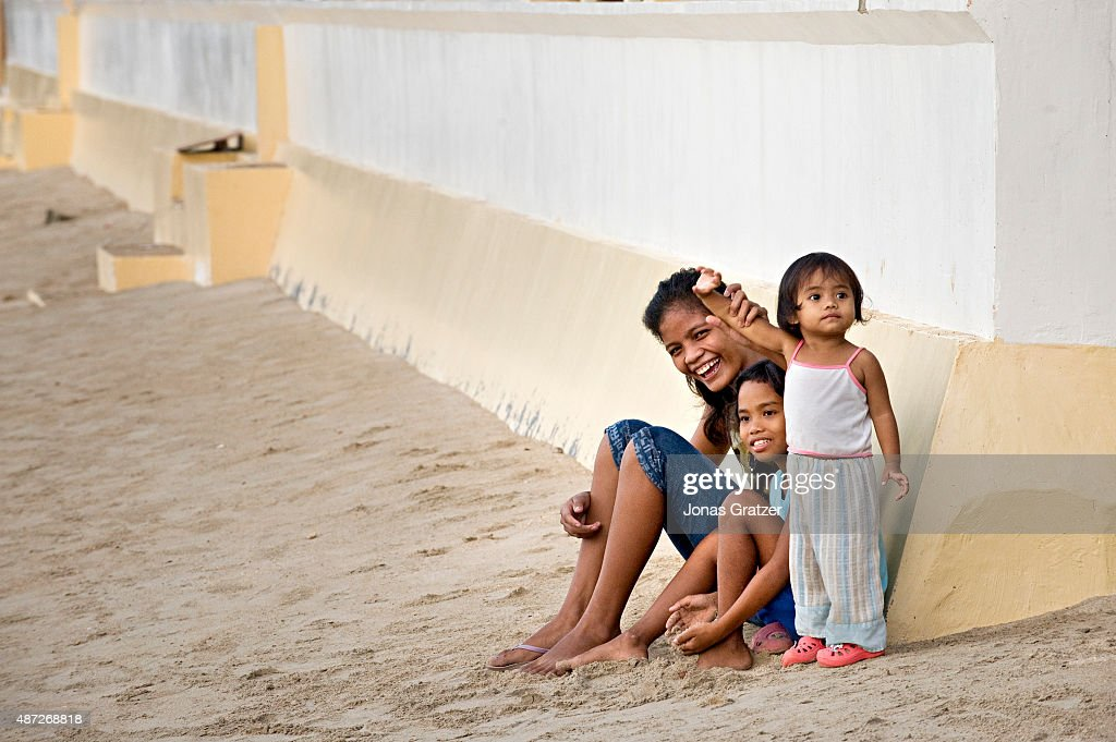 A family enjoys the sunset on the beach at El Nido, a