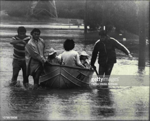 A family evacuated from a threatened home in hauled to safety in a boat in Oakes Road Old Toongabbie today March 20 1978