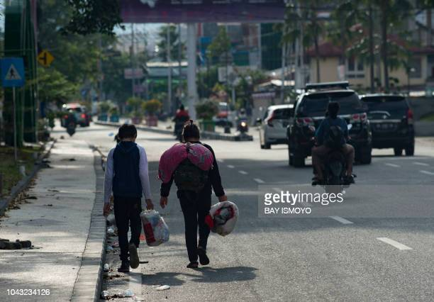 A family evacuates Palu in Central Sulawesi on September 30 after a strong earthquake trigered a tsunami that struck the area The death toll from a...
