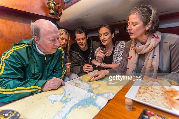 Family Examining a Map Below Decks on a Sailing Boat