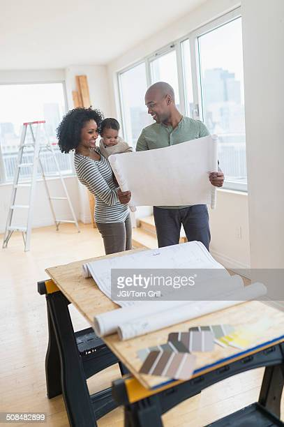 family examining blueprints in new home - build grill stock photos and pictures